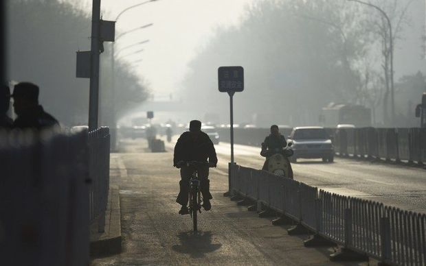 A cyclist rides in a cycle lane on a polluted morning in Beijing on April 7, 2016.