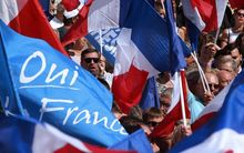 "French far-right party Front National (FN)'s supporters hold French National flags and FN's flags as they listen to their president near a banner which translates as ""Marie saves France"" on September 3, 2016 during a FN"