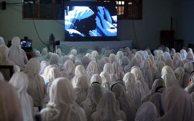 Indian Nuns from the Catholic Order of the Missionaries of Charity, watch a live telecast of the canonisation of Mother Teresa from Rome, at The Mother House in Kolkata