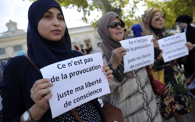 "Women hold signs reading ""Is it not a provocation, just my freedom of conscience"" during a ""headscarf march"" in Avignon, southern France."
