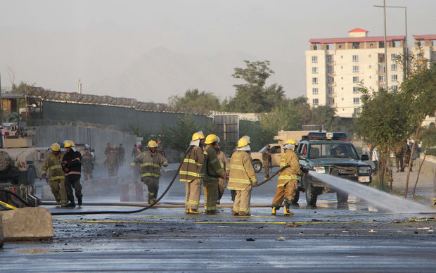 Firefighters clear debris after double suicide attacks killed at least 24 people in Kabul outside the Defence Ministry.