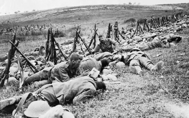 Men of the Royal Warwickshire Regiment, their rifles stacked nearby, lying exhausted in the grass in a rear area.