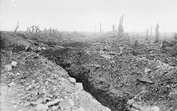The badly shelled main road to Bapaume through Pozieres, showing a communication trench and broken trees.