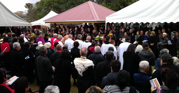 Mourners stand as the casket is taken from the marae.