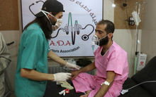 A doctor treats a Syrian man suffering from breathing difficulties at a make-shift hospital in Aleppo after regime helicopters dropped barrel bombs on the rebel-held Sukkari neighbourhood of the northern Syrian city on September 6, 2016.