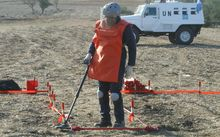 A UN expert works to dispose of landmines.