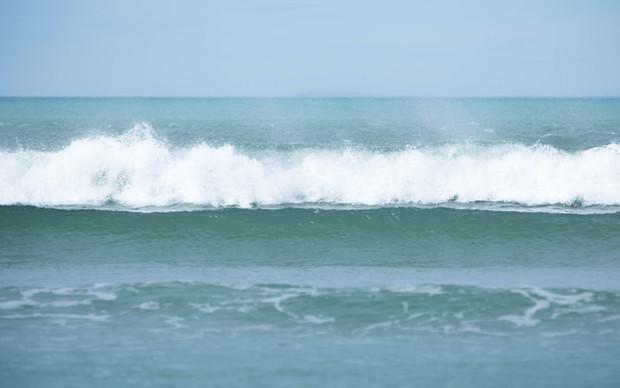 Waves break at a beach.