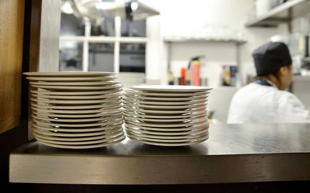 Stack of plates on shelf in commercial kitchen