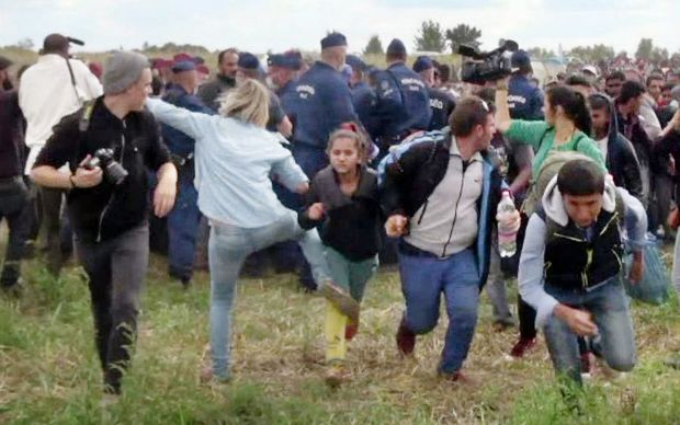 This video grab made on September 9, 2015 shows a Hungarian TV camerawoman kicking a child as she run with other migrants from a police line during disturbances at Roszke, southern Hungary.