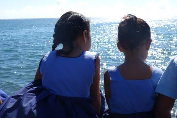 Young schoolgirls sit on the foreshore in Apia