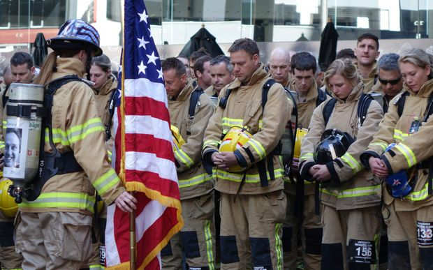 Firefighters bow their heads ahead of beginning the climb up Auckland's Sky Tower in honour of those who lost their lives in New York on 11 September 2001.