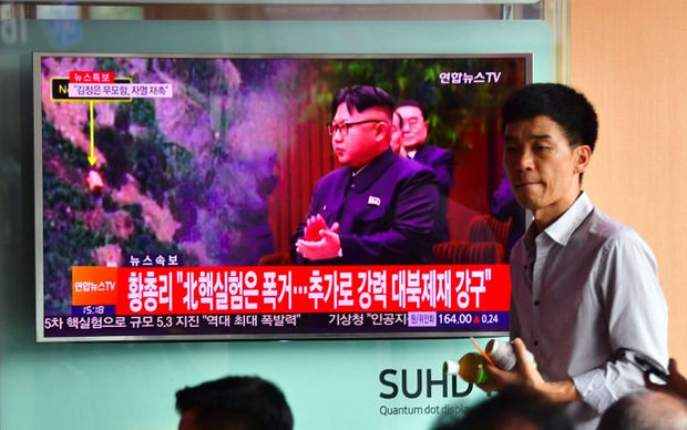 People watch a television news report, showing file footage of North Korean leader Kim Jong-Un, at a railway station in Seoul on September 9, 2016. North Korea claimed September 9 it has successfully tested a nuclear warhead that could be mounted on a missile,