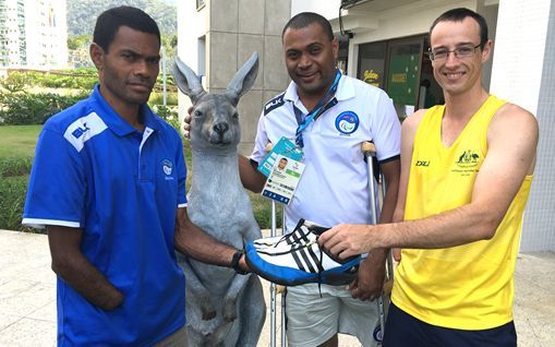 Fiji high jumper Epeli Baleibau (L) is presented with his new shoes by Australia's Aaron Chatman (R).