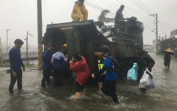 Locals affected by super typhoon Meranti are evacuated on a military armoured vehicle in southern Pingtung county in Taiwan.