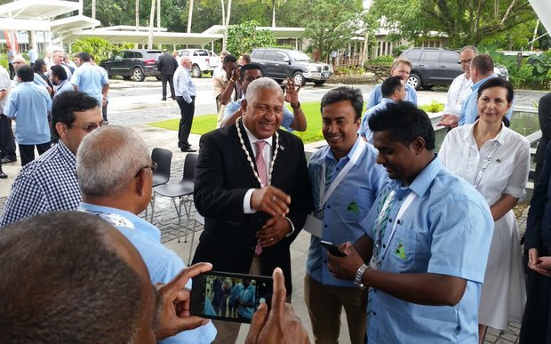 The Fiji Prime Minister Frank Bainimarama meets local & international business people in Fiji at the Fiji/Australia Business council Forum while Australian dignitaries look on.