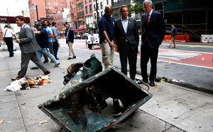 New York Mayor Bill de Blasio (centre) and New York Governor Andrew Cuomo (right) stand in front of a mangled dumpster while touring the site of the explosion in the Chelsea neighborhood of New York.