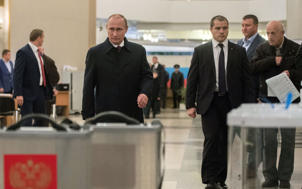 Russian President Vladimir Putin, foreground left, casts his vote at Polling Station No. 2151 at the Russian Academy of Sciences on Unified Election Day.