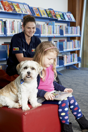 Ivy reads to Charlie Brown, watched by Waikato District Council animal control manager Megan May.