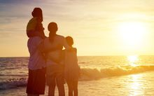 Family standing on a beach looking at the sunset. (file).