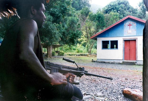 Photo taken on the 20th of July 2003. A militiaman loyal to renegade warlord Harold Keke guards the church where hostages Father Peter Kesimo, Father Alfred Tabo and Father Benjamin Kunu are being held in the Guadalcanal Liberation Front stronghold of Mbiki on the remote Weather Coast.
