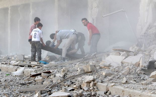 Rescue workers move an injured man from the rubble after airstrike in the Al-Ansari district of Aleppo.