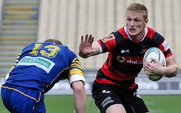 Johnny McNicholl of Canterbury looks to fends off Matt Faddes of Otago.