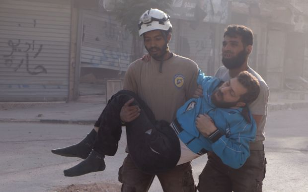 Residents of Aleppo carry an injured man after air strikes on the city.