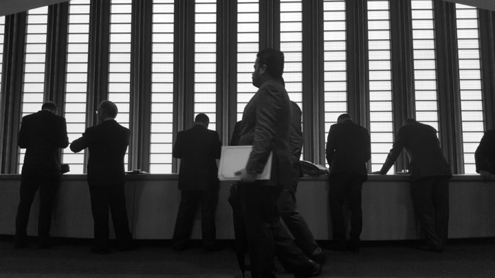 A silhouette of men in suits against a window at the United Nations in New York