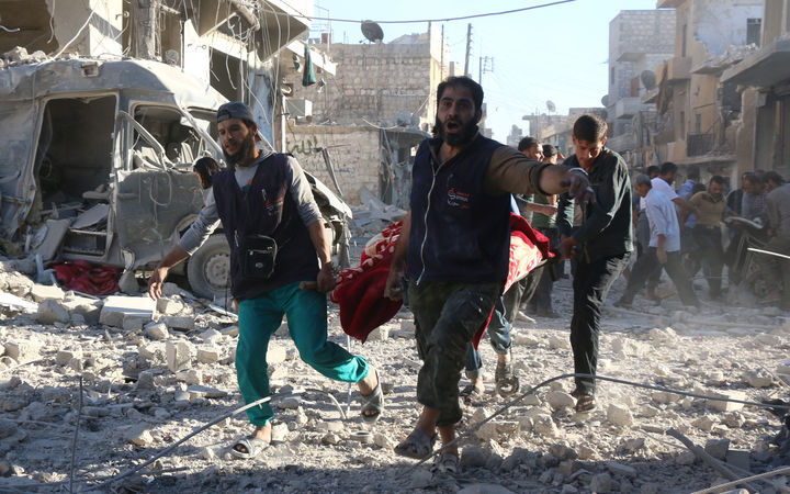 Volunteers carry out the wounded after government forces bombard rebel-held Heluk district in Aleppo.