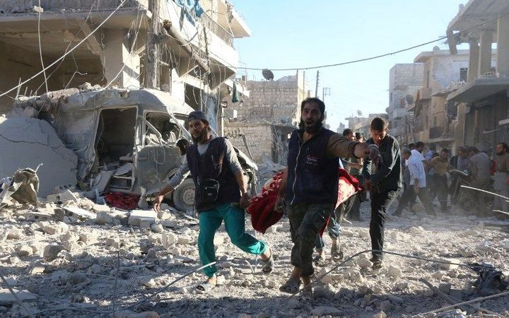 Syrian volunteers carry an injured person on a stretcher following Syrian government forces airstrikes on the rebel held neighbourhood of Heluk in Aleppo.