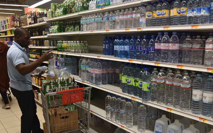 A worker fills shelves with water bottles at a supermarket in the commune of Petion Ville, in the Haitian Capital Port-au-Prince, on October 2, 2016.