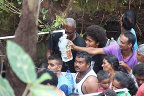 People crowd to fill bottles with water from the Natadradave stream.