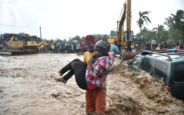A woman is carried across the river La Digue in Petit Goave where the bridge collapsed during the heavy rain, southwest of Port-au-Prince.