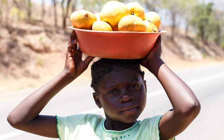 An African girl carrying a basket on her head. Zambia