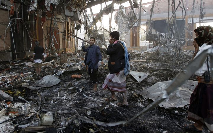 Yemeni rescue workers search for victims amid the rubble of a destroyed building following attacks blamed on Saudi-led coalition air strikes in the capital Sanaa.