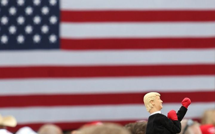 A supporter of Republican presidential nominee Donald Trump holds up a boxing hand-puppet in his likeness.