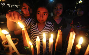 Girls in the southern Thai province of Narathiwat light candles to the late king,  Bhumibol Adulyadej