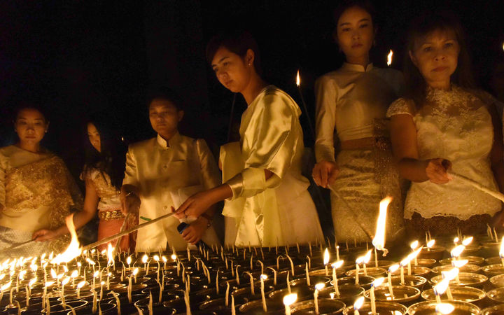 Thai devotees light candles for their late King Bhumibol Adulyadej in Bodhgaya, India.