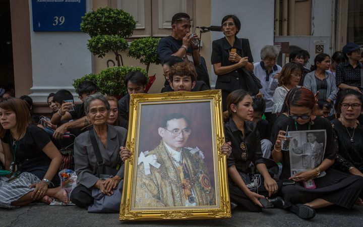 Thai Royalists and well-wishers gather inside Siriraj Hospital while carrying portraits of the King to await the funeral procession.