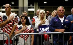 Supporters of Donald Trump stand for the Pledge of Allegiance as they wait for Trump's arrival at a rally at the Charlotte Convention Center.