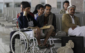 Yemeni men wounded in the Saudi-led coalition strike on a funeral last weekend wait for an Omani plane to evacuate them.