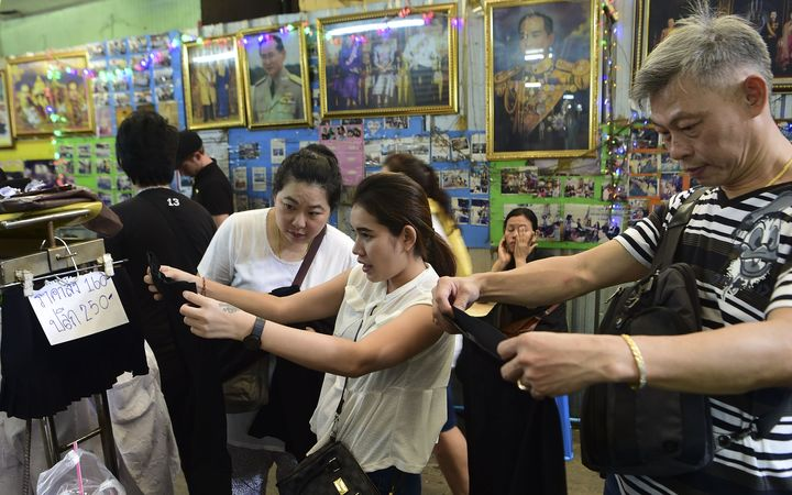 Mourners browse black dresses in a shop next to photos of the late Thai King Bhumibol Adulyadej in Bangkok on October 15, 2016.