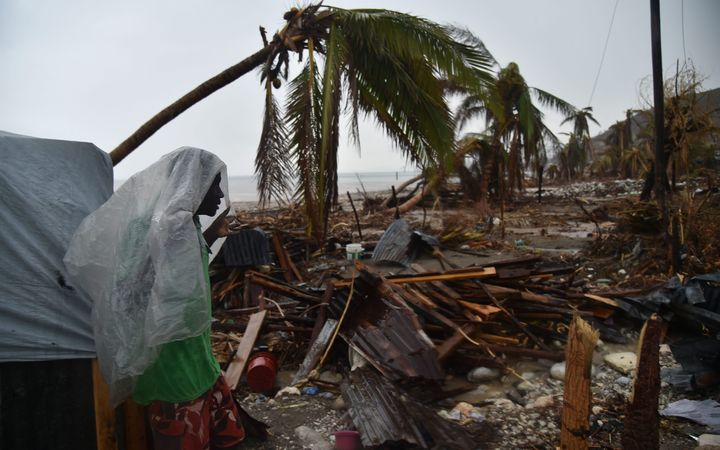 Hurricane Matthew victim James stands under the rain in front of his destroyed house in Port-a-Pimet, Les Cayes.