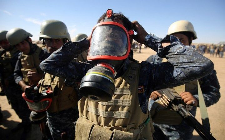 An Iraqi policeman tries on a gasmask at the Qayyarah military base, about 60 kilometres (35 miles) south of Mosul, on October 16, 2016, as they prepare for an offensive to retake Mosul, the last IS-held city in the country,