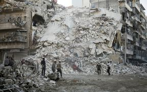 Members of the Syrian Civil Defence, known as the White Helmets, search for victims amid the rubble of a destroyed building following reported air strikes in the rebel-held Qatarji neighbourhood of the northern city of Aleppo on Monday.