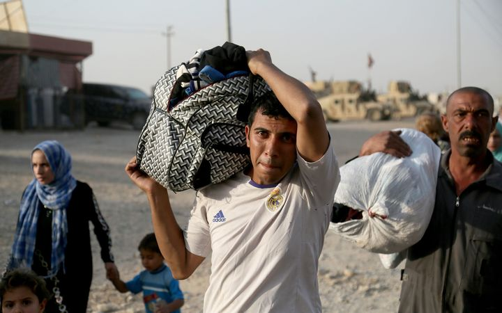 Iraqis fleeing from IS controlled areas of Mosul arrive at Al Qayyarah, a town secured by the Iraqi Army.