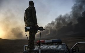 A member of the Iraqi government forces takes a position on top of a vehicle as smoke rises on the outskirts of the Qayyarah area, some 60km south of Mosul