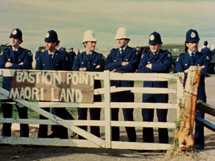 "A sign says ""Bastion Point Maori Land"" 6 police officers are standing behind the fence and sign."