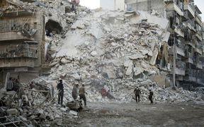 Members of the Syrian Civil Defence, known as the White Helmets, search for victims amid the rubble of a destroyed building following reported air strikes in the rebel-held Qatarji neighbourhood of the northern city of Aleppo, on October 17, 2016.