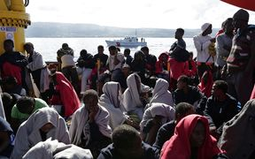 This handout picture taken and released by the Italian Red Cross on October 22, 2016 shows migrants landing in Vibo Marina, after a rescue operation in the Mediterranean Sea.
